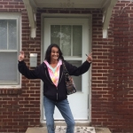 IL Consumer standing in front of her new home smiling big!