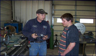 Mentor with Morgan Diesel of Pratt explains welding equipment parts to a local Student Mentee interested in becoming a Welder at the DMD 2009 worksite.