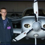 Local Student Mentee from Norwich interested in becoming a pilot poses in front of small two-seater airplane at the Pratt County Airport job shadow.